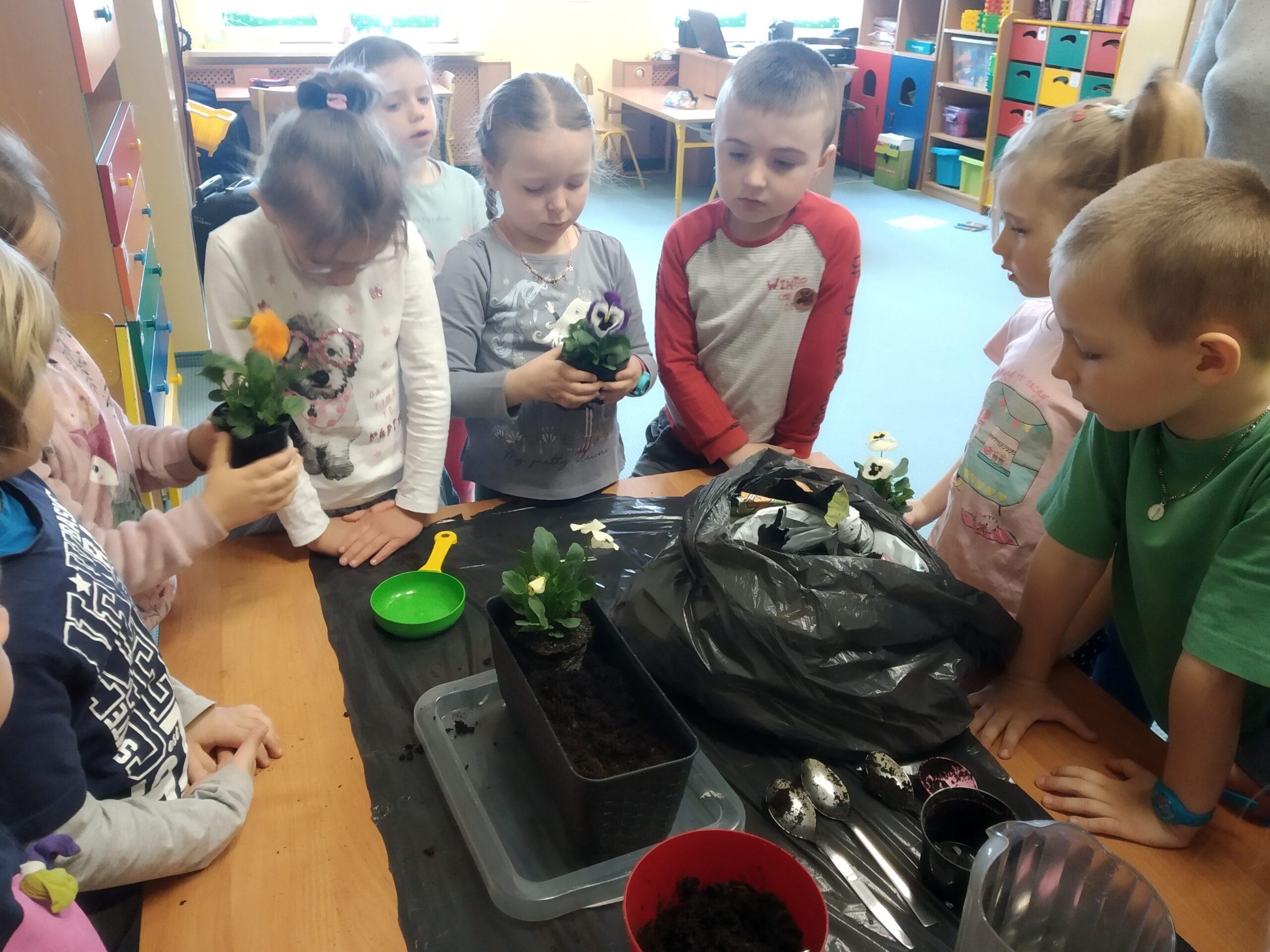 Zdjęcie przedstawiające zdjęcie dzieci sadzących kwiaty.