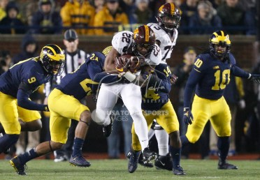 Nov 4, 2017; Ann Arbor, MI, USA; Minnesota Golden Gophers running back Kobe McCrary (22) runs the ball against Michigan Wolverines defensive back Josh Metellus (14) during the second quarter at Michigan Stadium. Mandatory Credit: Raj Mehta-USA TODAY Sports