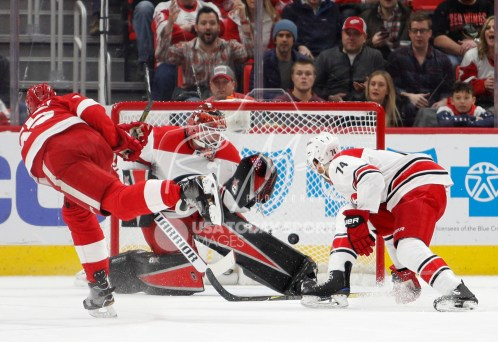 Feb 24, 2018; Detroit, MI, USA; Detroit Red Wings defenseman Danny DeKeyser (65) scores a goal on Carolina Hurricanes goaltender Scott Darling (33) during the first period at Little Caesars Arena. Mandatory Credit: Raj Mehta-USA TODAY Sports