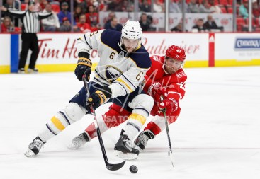 Feb 22, 2018; Detroit, MI, USA; Buffalo Sabres defenseman Marco Scandella (6) beats Detroit Red Wings left wing Darren Helm (43) to the puck during the second period at Little Caesars Arena. Mandatory Credit: Raj Mehta-USA TODAY Sports