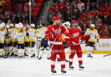 Feb 20, 2018; Detroit, MI, USA; Detroit Red Wings left wing Justin Abdelkader (8) and left wing Tomas Tatar (21) skate off the ice after the game as the Nashville Predators celebrate the win behind them at Little Caesars Arena. Mandatory Credit: Raj Mehta-USA TODAY Sports