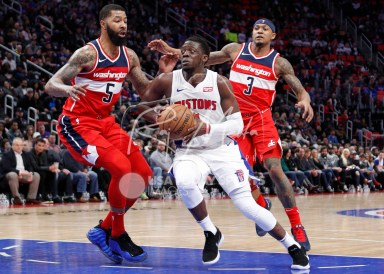 Mar 29, 2018; Detroit, MI, USA; Detroit Pistons guard Reggie Jackson (1) drives to the basket against Washington Wizards forward Markieff Morris (5) and guard Bradley Beal (3) during the fourth quarter at Little Caesars Arena. Mandatory Credit: Raj Mehta-USA TODAY Sports