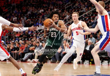 Feb 28, 2018; Detroit, MI, USA; Milwaukee Bucks guard Sterling Brown (23) drives to the basket against Detroit Pistons guard Luke Kennard (5) and forward Henry Ellenson (right) during the fourth quarter at Little Caesars Arena. Mandatory Credit: Raj Mehta-USA TODAY Sports
