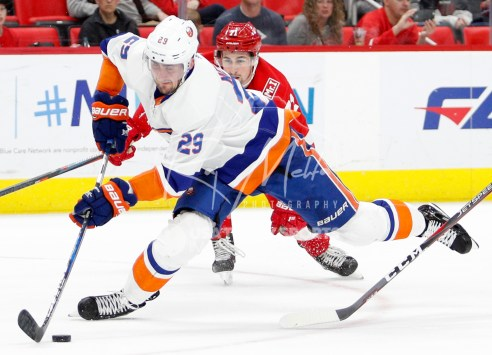 Apr 7, 2018; Detroit, MI, USA; New York Islanders center Brock Nelson (29) skates with the puck as he is tripped up by the stick of Detroit Red Wings right wing Anthony Mantha (right) during the third period at Little Caesars Arena. Mandatory Credit: Raj Mehta-USA TODAY Sports