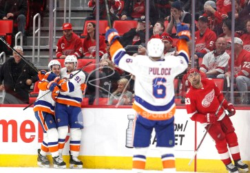 Apr 7, 2018; Detroit, MI, USA; New York Islanders center Mathew Barzal (13) hugs goal scorer center John Tavares (91) as defenseman Ryan Pulock (6) raises his arms in celebration in overtime against the Detroit Red Wings at Little Caesars Arena. Mandatory Credit: Raj Mehta-USA TODAY Sports