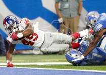 Aug 17, 2018; Detroit, MI, USA; New York Giants running back Robert Martin (49) dives for a touchdown over Detroit Lions defensive back Trey Walker (47) and defensive back Rolan Milligan (41) during the fourth quarter at Ford Field. Mandatory Credit: Raj Mehta-USA TODAY Sports