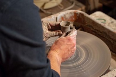 Potter making a raku vase on the pottery wheel.