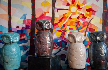 Raku pottery owls in front of a painting