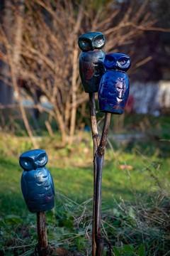 ceramic raku owls outside in a garden
