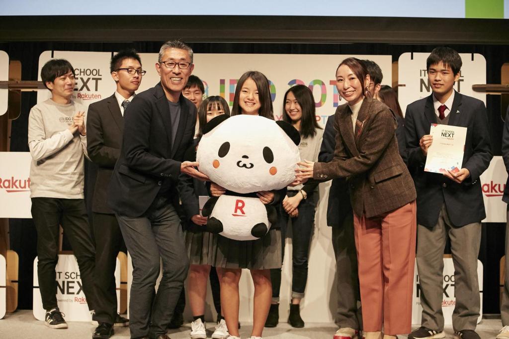 Hirai (left) and Rakuten Customer Strategy Department General Manager Madoka Yamaoka present the students of Yuki High School with a bonus prize: An oversized Rakuten Panda.
