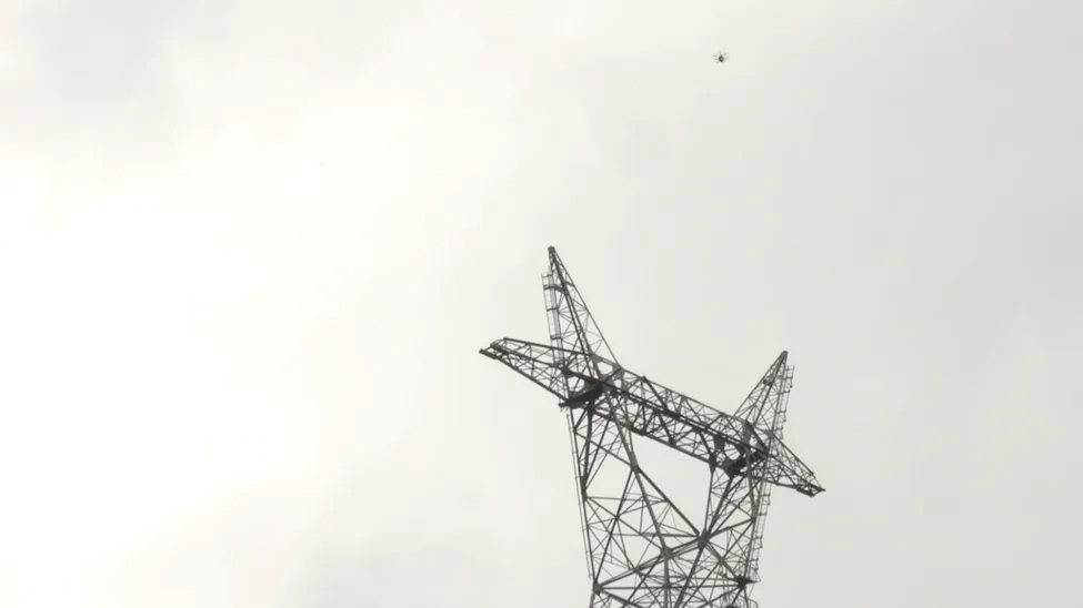 Just a speck: A Rakuten drone conducting a 'drone highway' test over power lines in rural Japan.