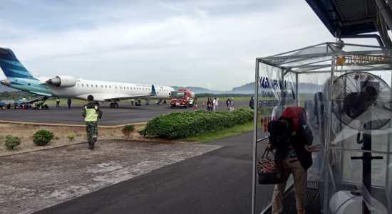 Seorang penumpang Garuda yang mendarat di Bandara DR FL Tobing Pinangsori, Tapteng, Selasa (12/5/2020) melintasi bilik penyemprotan. Foto: Istimewa