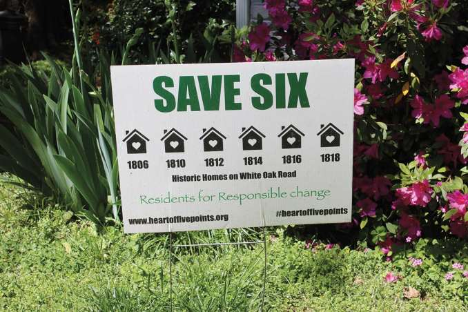 Yard signs urging the church to preserve the six homes