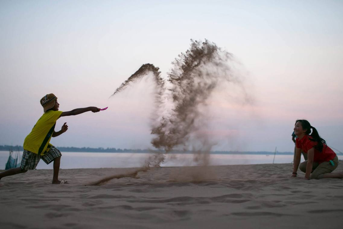 Children playing with sand, Mekong River, Laos.