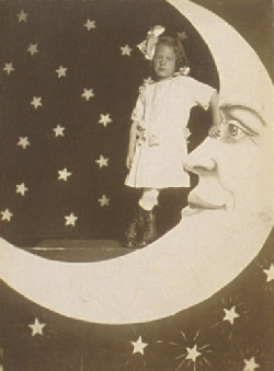 early studio portrait of a child leaning on the moon