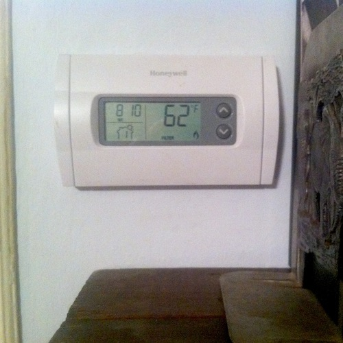Thermostat showing temperature of 62 degrees F
