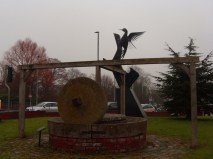 Photo of cider mill stone and woodpecker sculpture