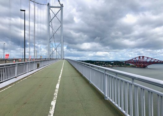 A footpath leads over a suspension bridge - the Forth Road Bridge. The bridge crosses the Firth of Forth, and the Forth Bridge can be seen in the distance as it reaches land in Fife.