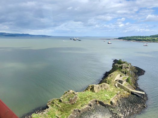 A small island with ruined buildings - Inchgarvie - in the Firth of Forth. Several ships of various sizes can be seen in the distance.
