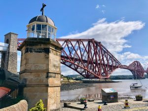 The world's smallest lighthouse can be seen, with the Forth Bridge looming large in the background.