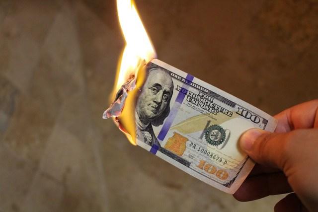 Burning hundred dollar bill