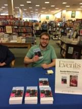 Writer Randal Eldon Greene holding a copy of his literary fiction novel Descriptions of Heaven.