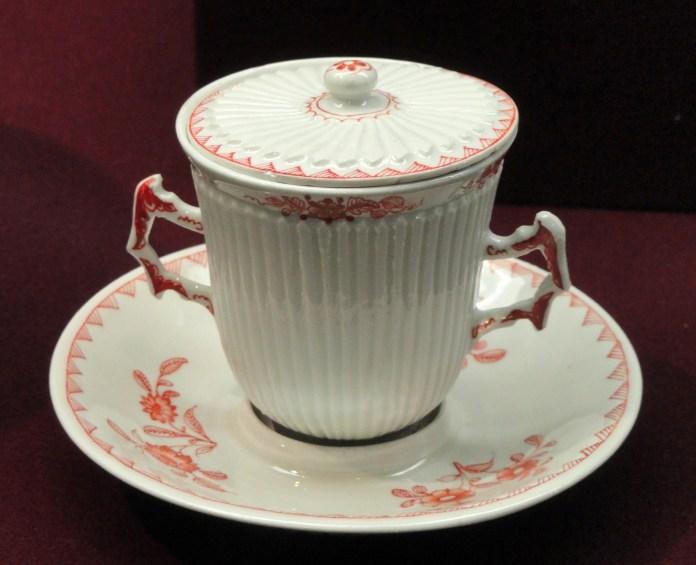 Covered_chocolate_cup_with_trembleuse_saucer,_c._1720,_Du_Paquier_factory,_hard-paste_porcelain,_iron-red_enamel_-_Gardiner_Museum,_Toronto_-_DSC00964