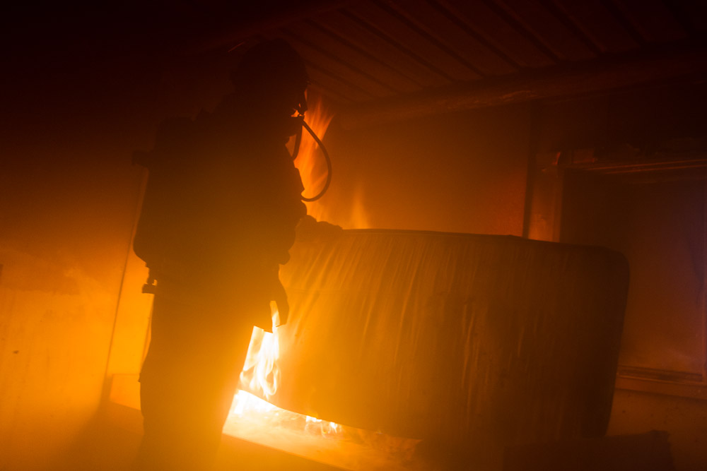 Firefighter inside a burning house