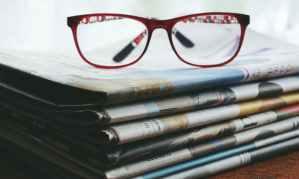 eye glasses on top of a stack of newspaper @randomnestfamily.