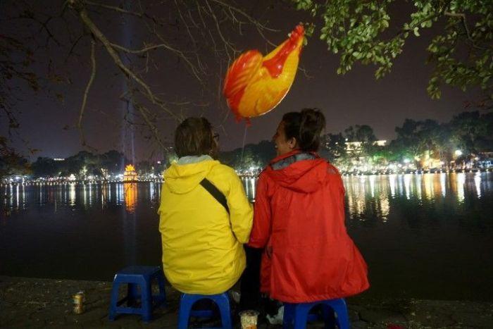 Inês y Chris frente al lago Hoán Kiem en la noche del Tet con el gallo Concoshí que nos acompañó toda la noche. El año nuevo chino es el año del galo y claro que compramos un globo :)