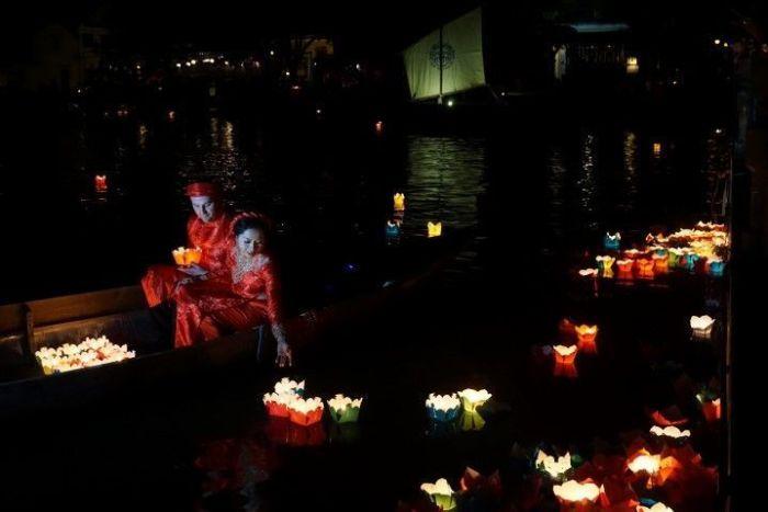 Novios en una barquita de Hoi An pidiendo deseos en el río Thu Bon