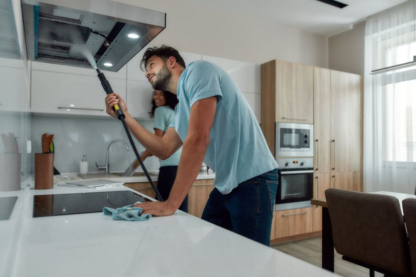 Young caucasian man in uniform cleaning kitchen range hood with steam cleaner while his smiling female colleague washing something in the sink on the background.