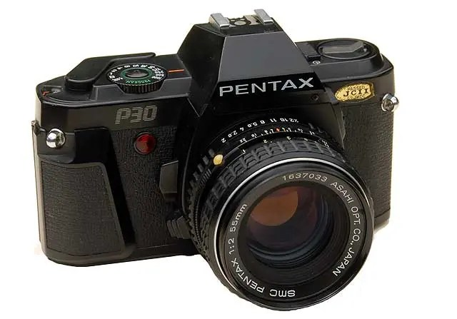 Pentax P30 mounted with an earlier SMC-Pentax-M 55mm f2 lens. The red light flashes when the timer is counting down. Below it on the lens housing is the depth of field preview button. Beneath that is the button to release the mechanism locking the lens to the camera.