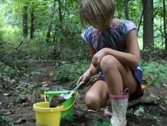 girl digging by stream