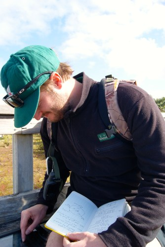 Kurt logging photographs and compass bearings at Rangitoto summit