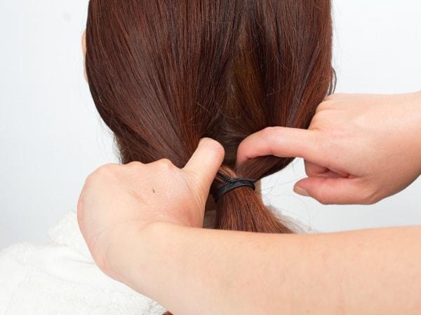 結わいてある部分を2つに割って、その中に毛束を入れ込んで、クルリンパ