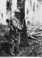 Australian-manned General Stuart M3 Light Tanks bust Japanese pillboxes in the final assault on Buna. NX105541 Private S. Sloss, 2/12th Battalion, leans nonchalantly against a coconut palm 40 yards away from a Jap pillbox which is being blasted by tankfire.
