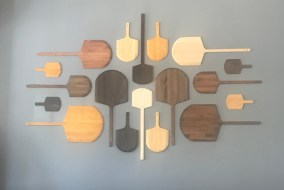 Pizza spatulas make up a pleasing to the eye display on one wall.