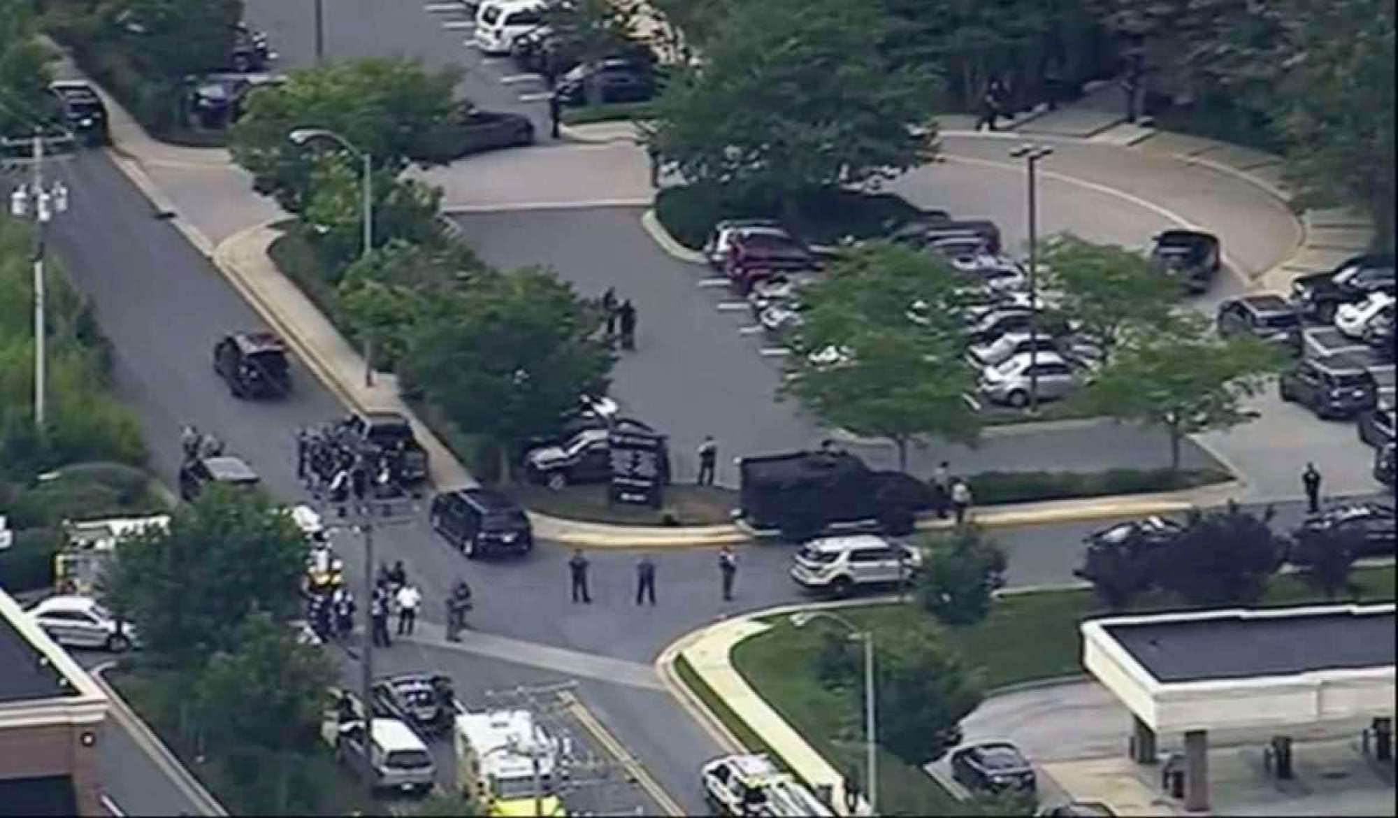 In this frame from video, people leave the Capital Gazette newspaper after multiple people have been shot on Thursday, June 28, 2018, in Annapolis, Md. (WJLA via AP)
