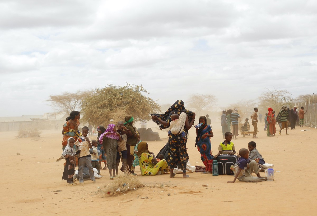 Newly arrived Somali refugees wait outside a UNHCR processing center at the Ifo refugee camp outside Dadaab, eastern Kenya, 100 kilometers (62 miles) from the Somali border. Human-induced climate change contributed to low rain levels in East Africa in 2011, making global warming one of the causes of Somalia's famine and the tens of thousands of deaths that followed, a new study has found — Aug. 5, 2011 (AP Photo/Jerome Delay)