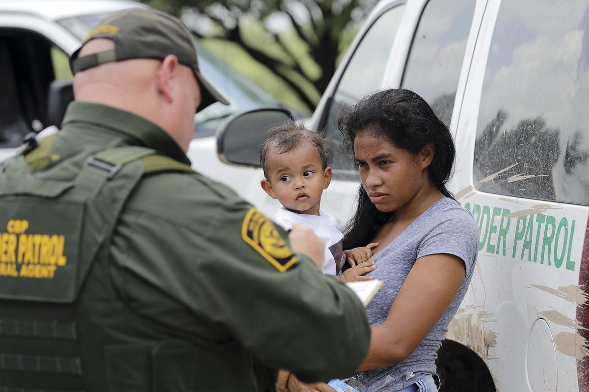 A mother migrating from Honduras holds her 1-year-old child as surrendering to U.S. Border Patrol agents after crossing the border Monday, June 25, 2018, near McAllen, Texas. (AP Photo/David J. Phillip)