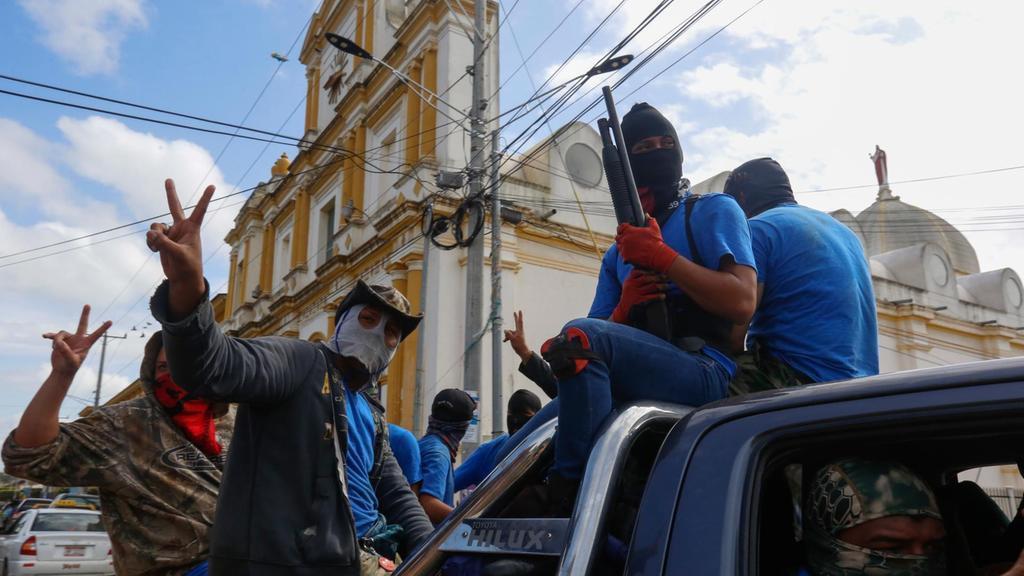 Armed pro-government militia members flash victory signs as they occupy the Monimbo neighborhood of Masaya, Nicaragua, Wednesday, July 18, 2018. (AP Photo/Alfredo Zuniga)