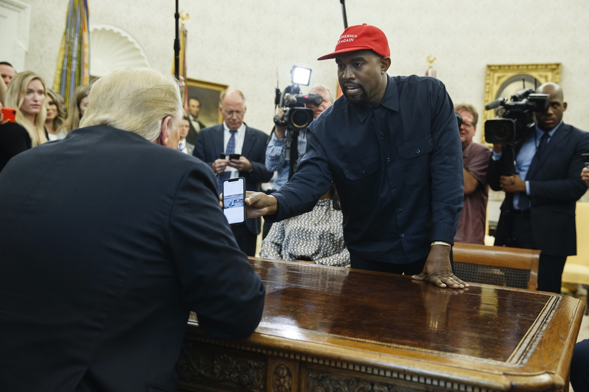 Kanye West shows President Donald Trump a photograph of a hydrogen plane during a meeting in the Oval Office of the White House, Thursday, Oct. 11, 2018, in Washington. (AP Photo/Evan Vucci)