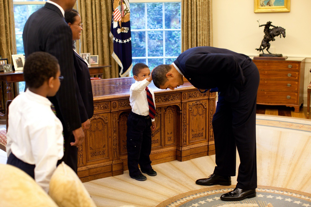 President Barack Obama bends over so the son of a White House staff member can pat his head during a visit to the Oval Office May 8, 2009. (Official White House Photo by Pete Souza)