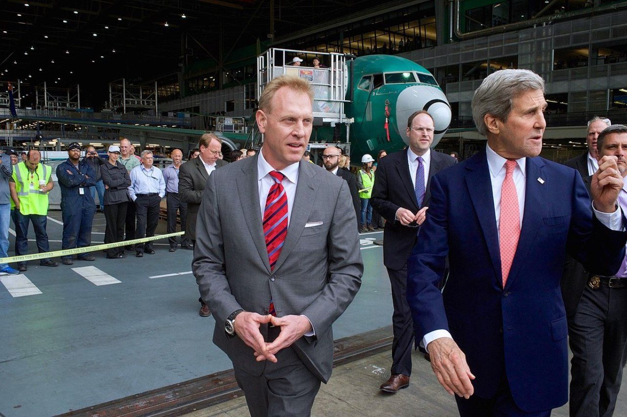 U.S. Secretary of State John Kerry speaks to Patrick Shanahan, senior vice president of Airplane Programs for Boeing Commercial Airplanes, before his speech focusing on U.S. and Pacific regional trade policy at the Boeing Co.'s 737 Airplane Factory in Renton, Washington on May 19, 2015. (State Department Photo/Public Domain)