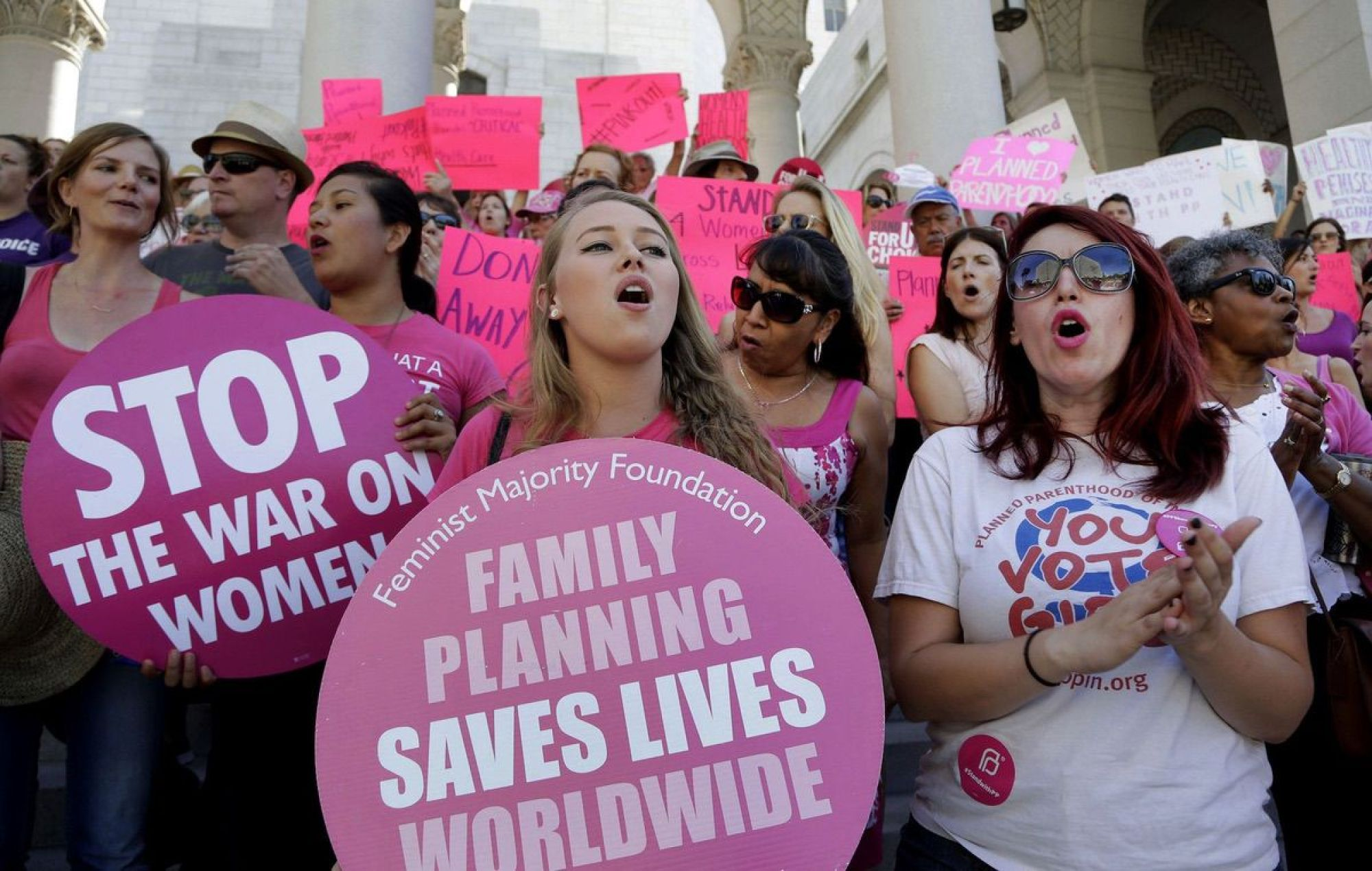 """Planned Parenthood supporters rally for women's access to reproductive health care on """"National Pink Out Day'' at Los Angeles City Hall - Sept. 9, 2015. (AP Photo/Nick Ut, File)"""
