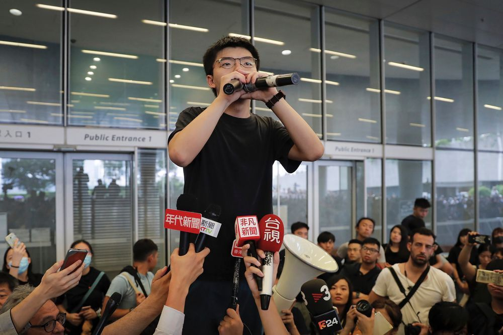 Pro-democracy activist Joshua Wong speaks to protesters near the Legislative Council in Hong Kong, Monday, June 17, 2019. (AP Photo/Kin Cheung)