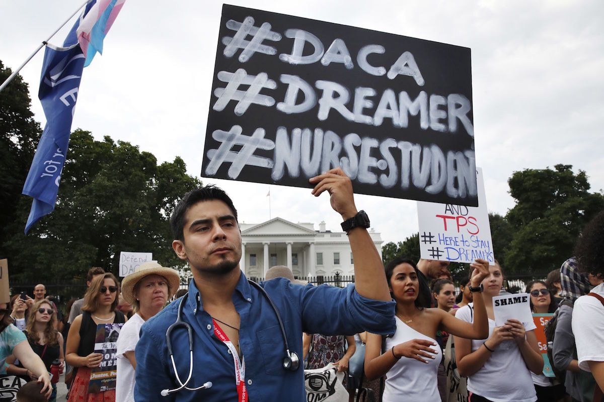 Carlos Esteban, 31, of Woodbridge, Va., a nursing student and recipient of Deferred Action for Childhood Arrivals, known as DACA, rallies with others in support of DACA outside of the White House, in Washington - Sept. 5, 2017 (AP Photo/Jacquelyn Martin)