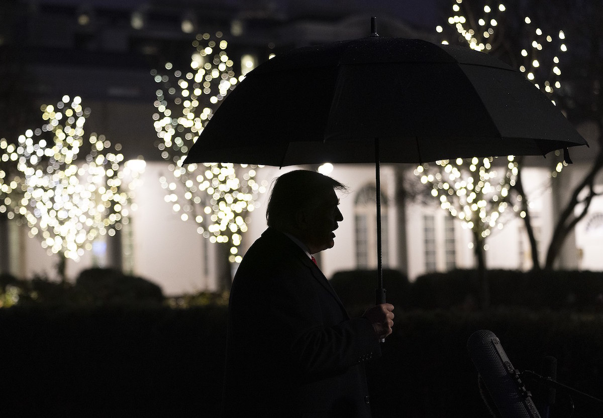 President Donald J. Trump is seen in silhouette holding an umbrella as he talks to members of the press on the South Lawn of the White House Tuesday, Dec. 10, 2019, prior to boarding Marine One to begin his trip to Hershey, Pa. (Official White House Photo by Joyce N. Boghosian)