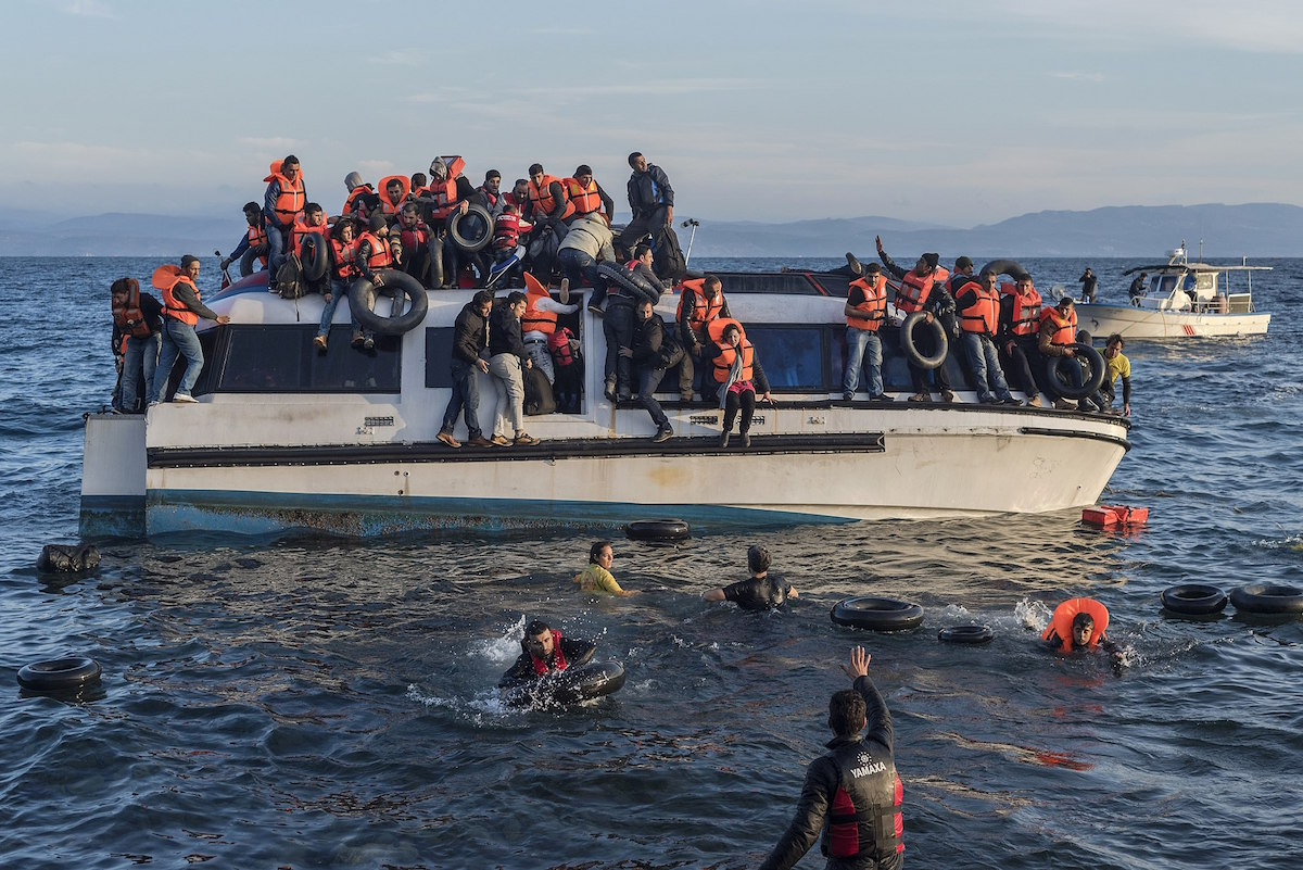 Syrian and Iraqi refugees arrive from Turkey to Skala Sykamias, Lesbos island, Greece. Volunteers (life rescue team – with yellow-red clothes) from the Spanish NGO Proactiva Open Arms help the refugees. – October 30, 2015 (Ggia/Creative Commons)